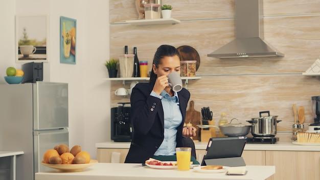 Freelancer trinkt morgens kaffee auf der tischplatte während des frühstücks mit tablet-computer. geschäftsfrau, die die letzten nachrichten online liest, bevor sie zur arbeit geht, mit moderner technologie in der küche