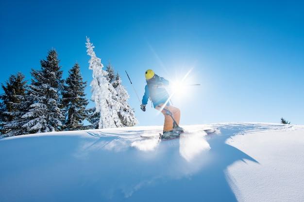 Freeride-skifahrer, die den hang in den bergen hinunterfahren