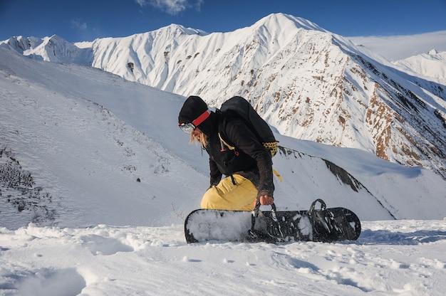 Freeride-snowboarder, der ein brett auf den bergen hält