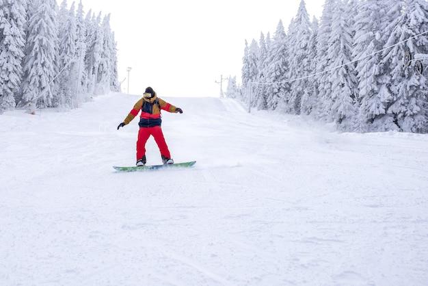 Freeride-snowboarder, der in einem bergskigebiet den hügel hinunterfährt