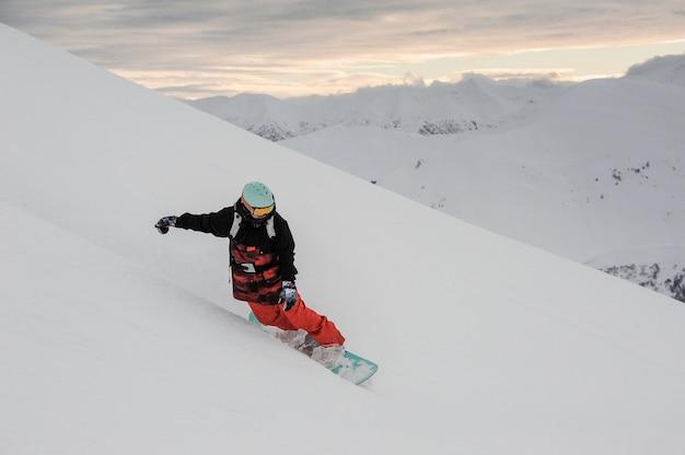 Freeride snowboarder rutscht den verschneiten hang hinunter