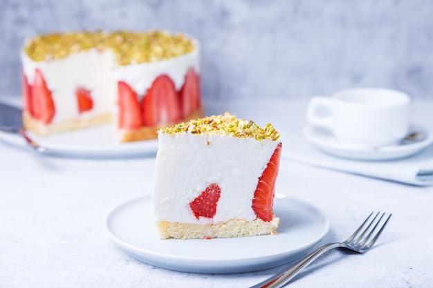 Freesier-kuchen mit frischen erdbeeren und pistazien. französisches klassisches dessert. portion kuchen auf einer weißen platte nahaufnahme.