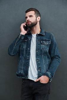 Freestyle junger mann steht isoliert auf grauer wand hand in der tasche und spricht selbstbewusst auf dem smartphone