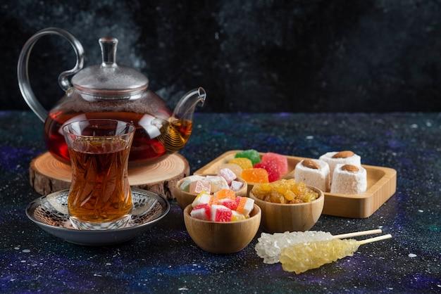 Fregrant tee mit süßen bonbons auf blauer oberfläche