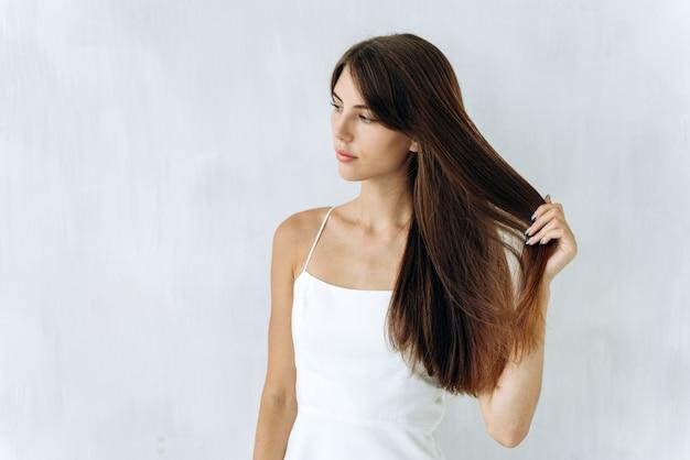 Frei wie der wind. porträt einer charmanten süßen frau steht und schaut weg, während sie die qualität ihres langen haares genießt. isolierter hintergrund