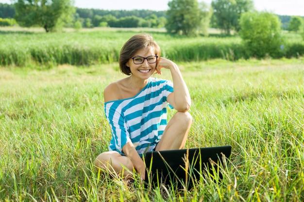Freiberufler-bloggerreisender der frau von mittlerem alter mit laptop auf natur