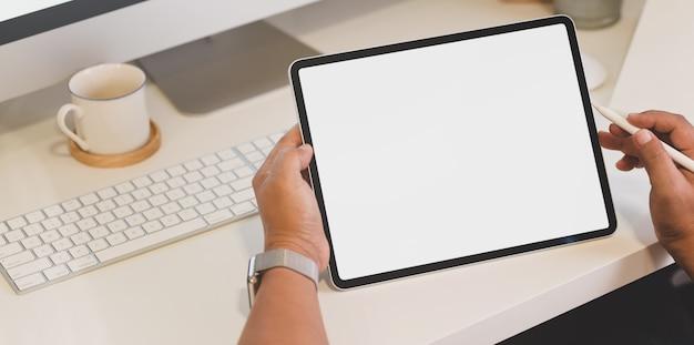 Freiberufler, der an seinem projekt mit tablette des leeren bildschirms arbeitet