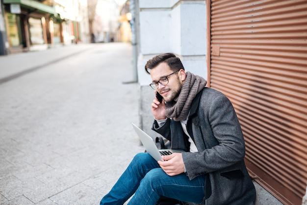 Freiberufler, der auf der straße spricht am handy und verwendet laptop sitzt.