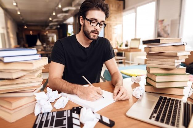 Freiberufler, der die kenntnisse sitzen am schreibtisch umgeben durch bücher nimmt.