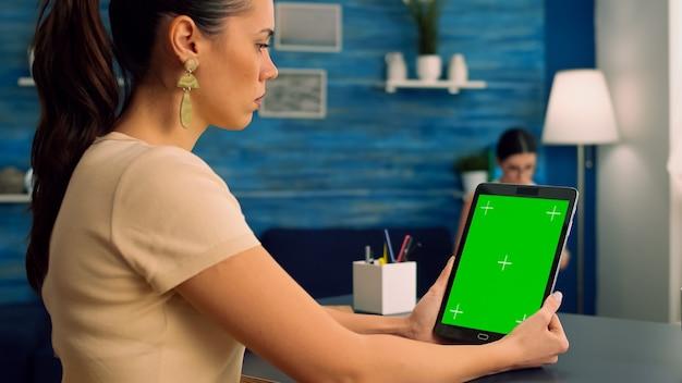 Freiberufler, der einen tablet-computer mit greenscreen-chroma-key-anzeige während des virtuellen meetings hält