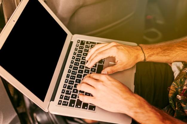 Freiberufler, der entfernt an laptop im auto arbeitet