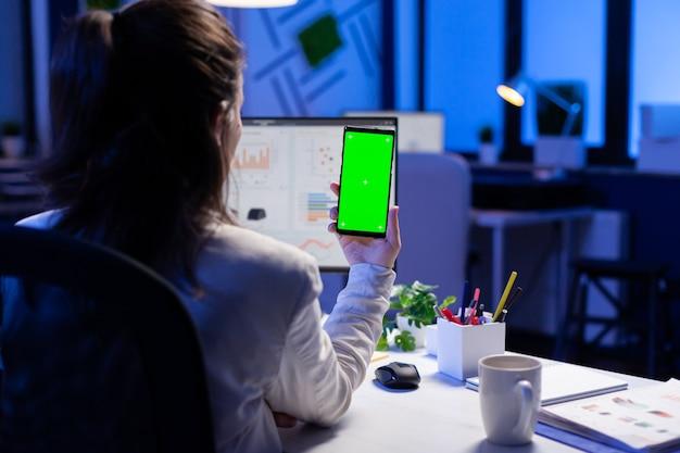 Freiberufler, der während des online-videoanrufs am schreibtisch im geschäftsbüro auf ein mobiltelefon mit greenscreen-display schaut
