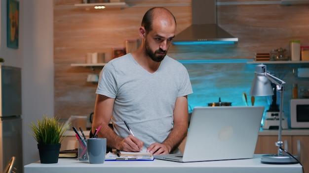 Freiberufler, der während des studiums notizen im notizbuch schreibt und moderne technologie verwendet, die zu hause überstunden macht. beschäftigter, fokussierter mitarbeiter, der modernes technologienetzwerk verwendet, drahtloses lesen, tippen, suchen