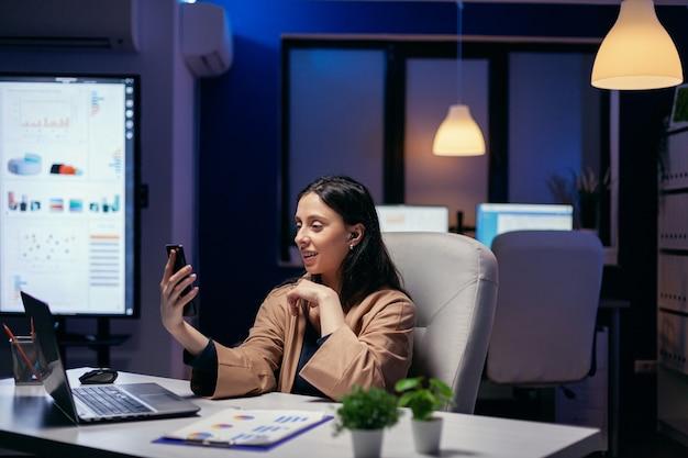 Freiberufler, der während eines virtuellen meetings um mitternacht an einem leeren arbeitsplatz spricht. frau, die während einer videokonferenz mit kollegen nachts im büro an finanzen arbeitet.
