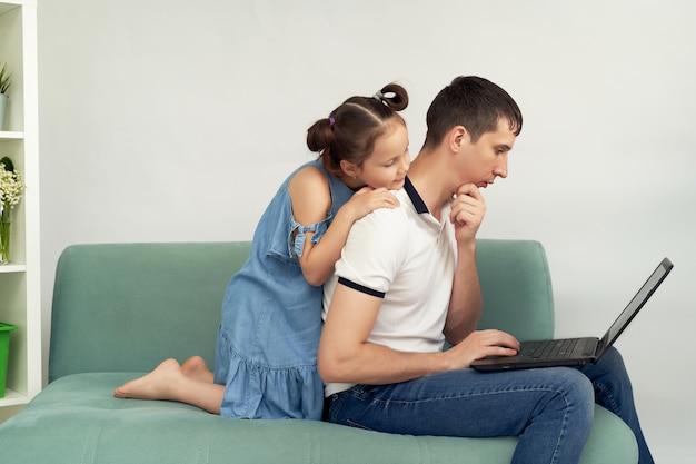 Freiberufler, der zu hause unter komfortablen bedingungen arbeitet. mann versucht zu arbeiten, kind verhindert, dass sein vater arbeitet.