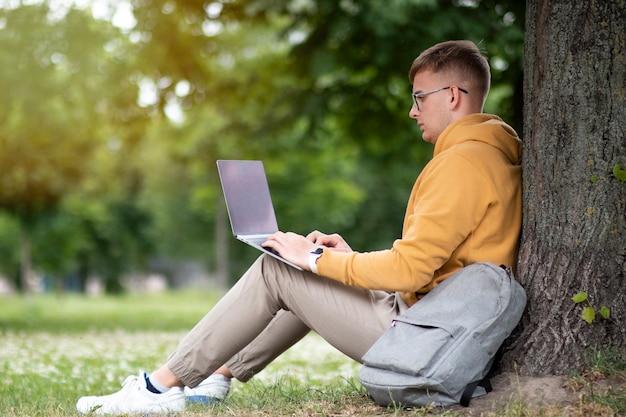 Freiberufler des jungen mannes arbeitet am laptop in den gläsern, die auf einem baum in einem park lehnen