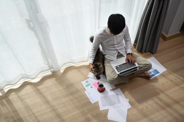 Freiberufler des jungen mannes, der mit seiner katze am laptop arbeitet, während sie zusammen im modernen raum sitzen.
