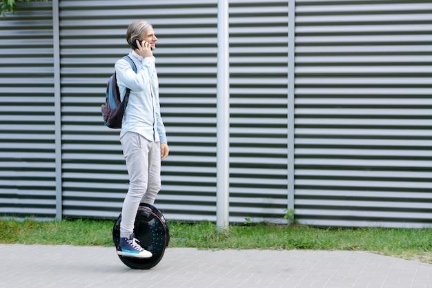 Freiberufler des modernen jungen erwachsenen männlichen geschäftsmannstudenten, der auf dem futuristischen ökologischen elektrischen einradroller des ökologischen elektrischen transports reitet und elektrisches rad mit smartphone balanciert. öko-planet.