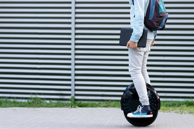 Freiberufler des modernen jungen erwachsenen männlichen geschäftsmannstudenten mit rucksack und laptop, die auf dem futuristischen ökologischen elektrischen einradroller des ökologischen elektrischen transports reiten, elektrisches rad balancierend. öko-planet.