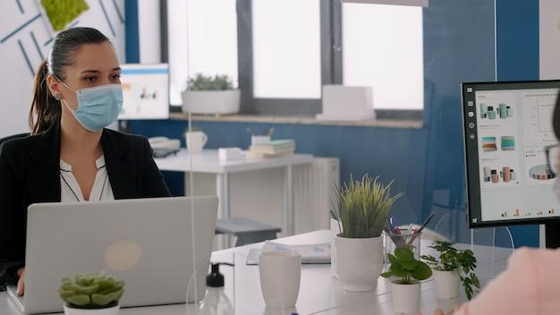 Freiberufler, die während der globalen pandemie gesichtsschutzmasken tragen, die am computer im geschäftsbüro arbeiten. team, das in einem neuen normalen büro sitzt und die soziale distanz respektiert, um eine infektion mit covid19 zu vermeiden