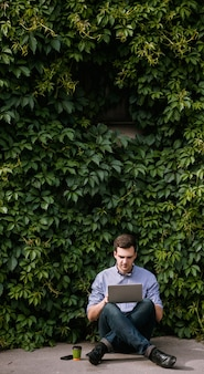 Freiberufler, introvertiert, der auf der straße arbeitet. kreativer aufgeschlossener mann, moderne technologie. naturkonzept