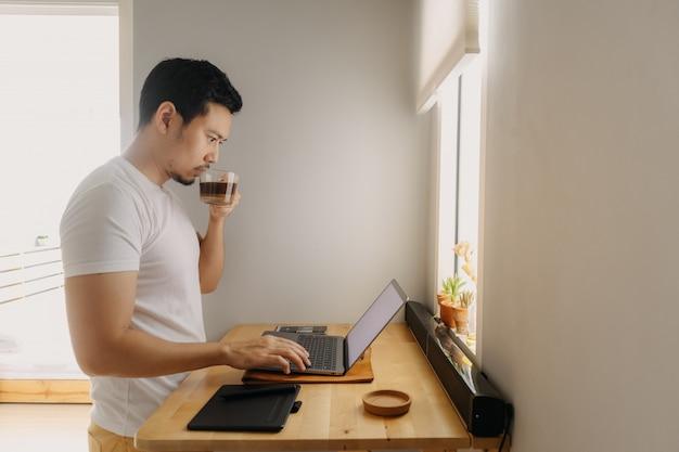 Freiberufler mann arbeitet an seinem laptop in seiner wohnung. konzept der freiberuflichen kreativen arbeiten.