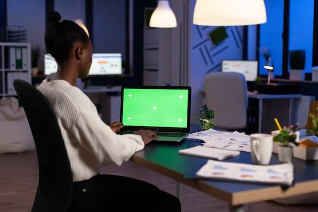 Freiberufler mit dunkler haut, der an einem laptop mit grünem bildschirm arbeitet, der spät in der nacht am schreibtisch im geschäftsbüro sitzt