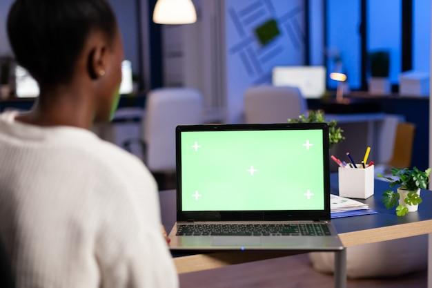 Freiberufler mit dunkler haut, der im büro überarbeitung mit grünem bildschirm macht, der spät in der nacht am schreibtisch im geschäftsbüro sitzt