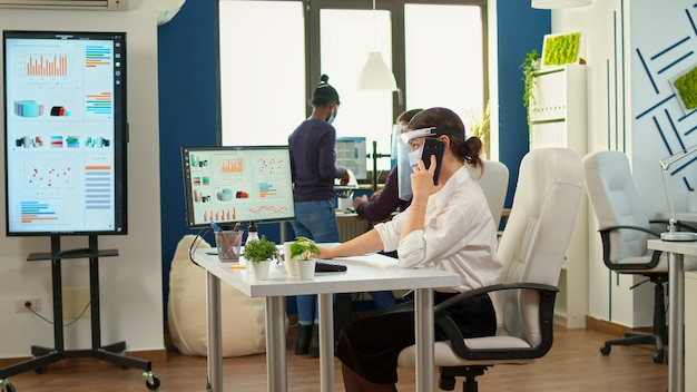 Freiberufler mit schutzmaske, der mit dem partner auf dem handy telefoniert, während der pandemie am schreibtisch im büroraum sitzt. multiethnische mitarbeiter, die in finanzunternehmen unter wahrung der sozialen distanz arbeiten