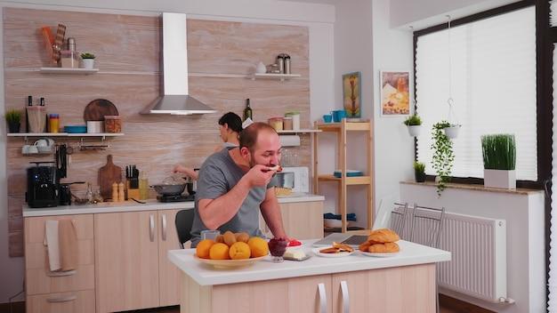 Freiberufler trinkt kaffee und arbeitet beim frühstück in der küche am laptop. unternehmer im schlafanzug, der von zu hause aus in der küche an einem laptop arbeitet.