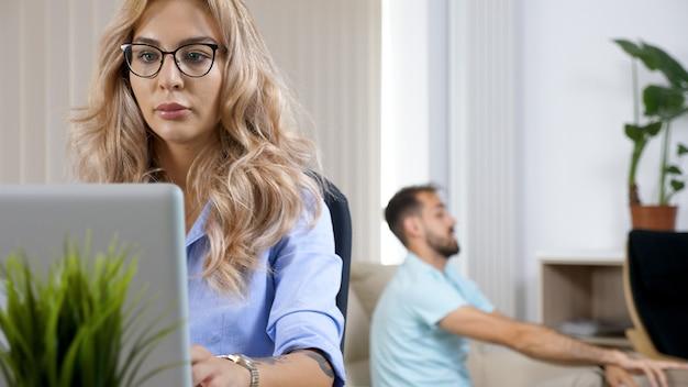 Freiberuflerin arbeitet am computer-laptop im haus, während der ehemann im hintergrund fernsieht