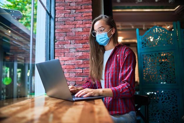 Freiberuflerin der jungen frau, die eine medizingesichtsmaske trägt, die entfernt an einem computer in einem café während einer pandemie arbeitet. soziale distanz und gesundheitsschutz vor viren an öffentlichen orten