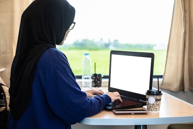 Freiberuflerin der muslime, die mit laptop in einem zug arbeitet.