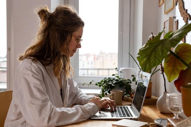 Freiberuflerin / designerin, die am computer vom heimbüro aus arbeitet. gemütlicher arbeitsplatz inmitten von pflanzen. heimarbeit