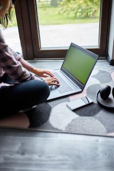 Freiberuflerin, die auf dem laptop tippt, der zu hause in der nähe großer fenster auf dem boden sitzt, zufriedene frau, die im notebook surft, studiert, von zu hause aus arbeitet.
