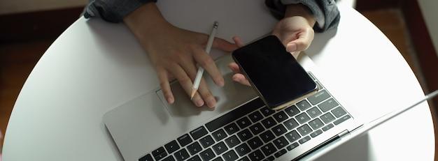 Freiberuflerin, die informationen auf dem smartphone beim arbeiten mit laptop auf couchtisch sucht