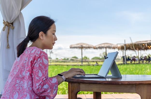 Freiberuflerin sitzt im café im freien und arbeitet am laptop