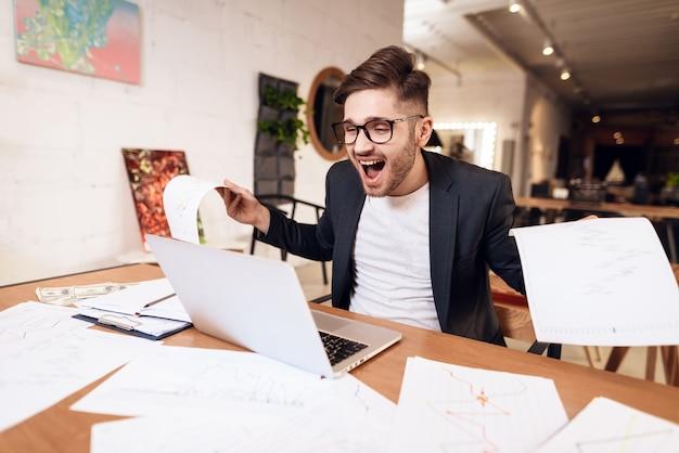 Freiberuflermann, der den laptop sitzt am schreibtisch glücklich betrachtet.