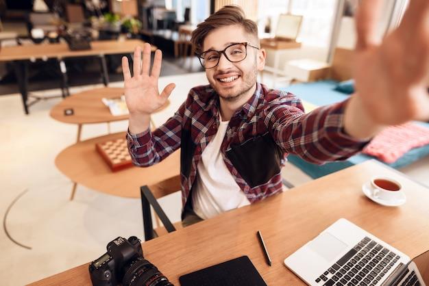 Freiberuflermann, der selfie am laptop sitzt am schreibtisch nimmt.