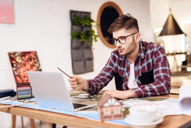 Freiberuflermannzeichnung auf plan am laptop, der am schreibtisch sitzt.