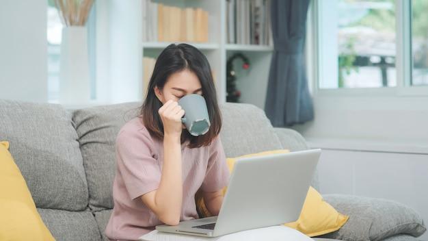 Freiberuflich tätige asiatin des jungen geschäfts, die an dem laptop überprüft social media und trinkenden kaffee beim lügen auf dem sofa arbeitet, wenn sie sich im wohnzimmer zu hause entspannen. lebensstilfrauen am hauskonzept.