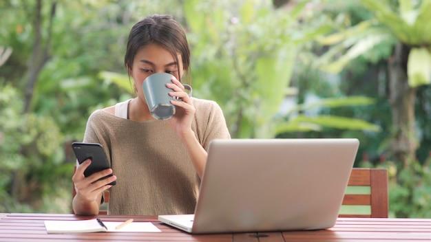 Freiberuflich tätige asiatin, die zu hause arbeitet, die geschäftsfrau, die an laptop arbeitet und den trinkenden kaffee des handys sitzt auf tabelle im garten am morgen verwendet.