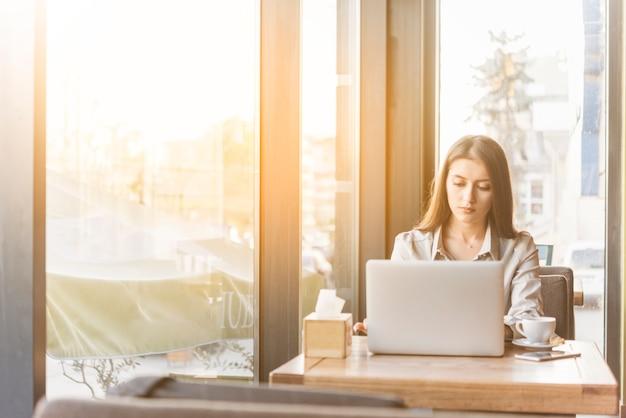 Freiberuflich tätige frau, die mit laptop in der kaffeestube arbeitet