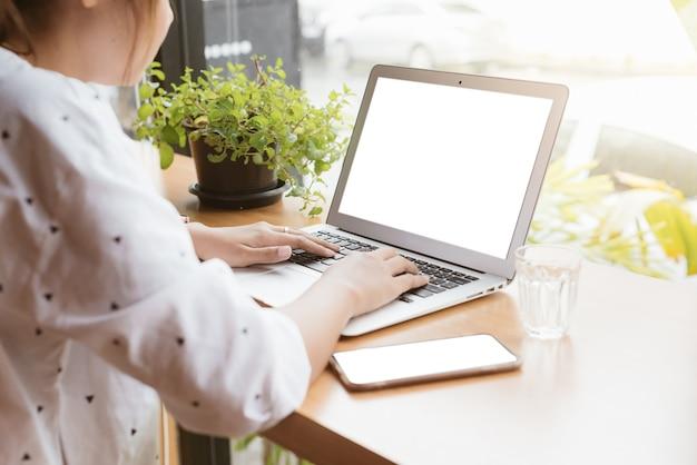 Freiberuflich tätiges arbeiten der asiatin mit laptop des leeren bildschirms.