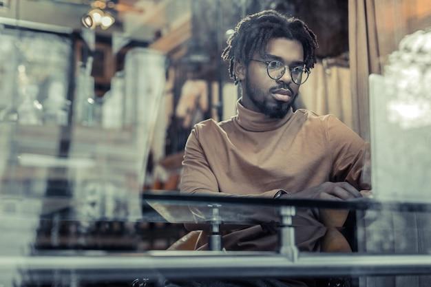 Freiberufliche arbeit. aufmerksamer geschäftsmann, der brille trägt, während mit computer arbeitet