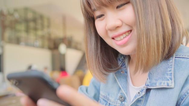 Freiberufliche asiatin des geschäfts, die smartphone für das sprechen, lesen und simsen beim sitzen auf tabelle im café verwendet. intelligente schönheiten des lebensstils, die an den kaffeestubekonzepten arbeiten.
