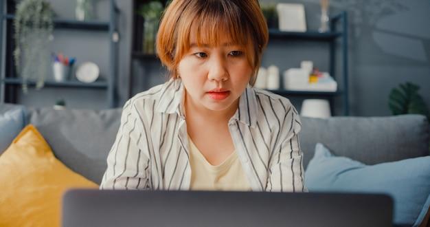 Freiberufliche asiatische dame freizeitkleidung mit laptop online-lernen im wohnzimmer zu hause