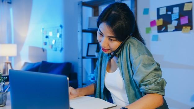 Freiberufliche asiatische frauen, die laptop verwenden, sprechen am telefon beschäftigter unternehmer, der entfernt im wohnzimmer arbeitet.