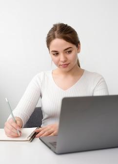 Freiberufliche frau am schreibtisch, die in der tagesordnung schreibt
