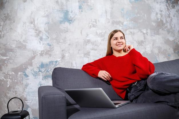 Freiberufliche frau, die auf einem sofa in einem gemütlichen zuhause sitzt und aus der ferne an einem modernen laptop arbeitet, erfahrene frau, die online-webinare auf der website ansieht. arbeiten von zu hause während der quarantäne